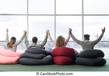 Cheerful Businesspeople Group In Coworking Center Team Coworkers Raised Hands Sitting in front Big Panoramic Window