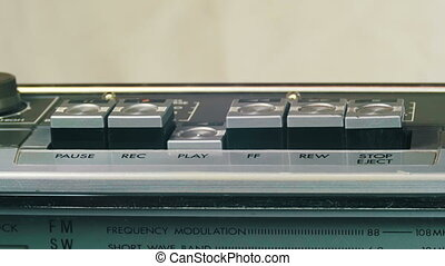 Pushing Play, Stop, Rec, Forward, Rewind Button on a Vintage Tape Recorder.
