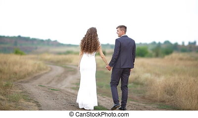 bride and groom are walking along the path in the field.