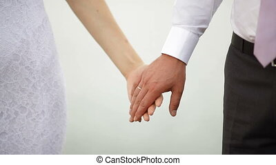 bride and groom hold hands on a wedding walk