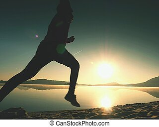 Silhouette of active athlete runner running on sunrise shore. Morning healthy lifestyle exercise