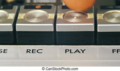Finger Presses Playback Control Buttons on Audio Cassette...