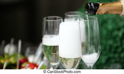 Pouring celebratory champagne into glasses. Bubbles of...