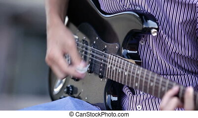 men hands guitarist playing guitar outdoor. close-up - men...