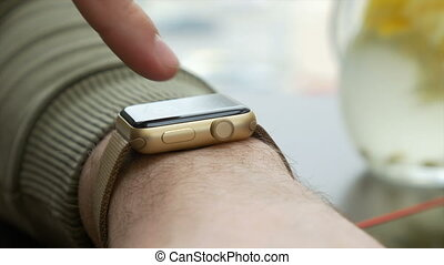 Close up view of man making touch gestures on a wearable smart watch computer device