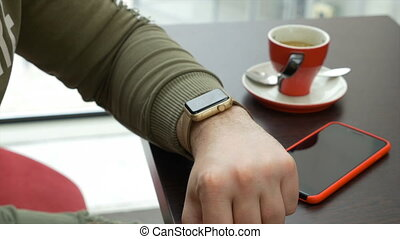 Young man using smartwatch email app while sitting at coffee...