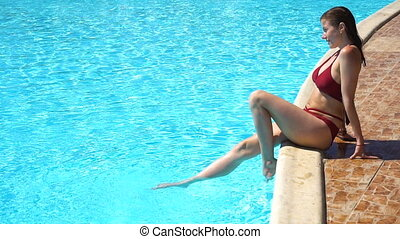 Woman in summer sitting on edge of swimming pool and play...