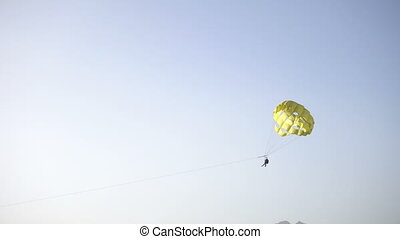 Parasailing over sea in blue sky with yellow parachute