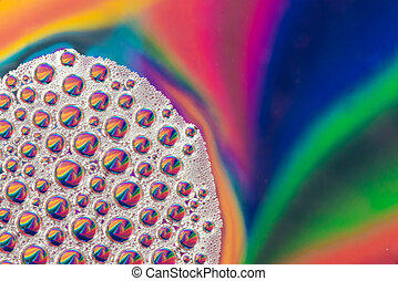 Dish soap water bubbles on rainbow colored background