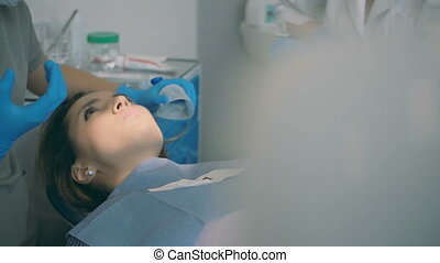Young woman lying in dental chair and hearing the doctor. Dentist with dental nurse advise the patient.