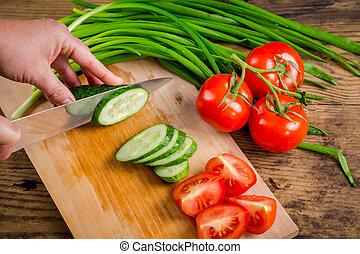Cut cucumber on wooden cutting board, above view - Cut...