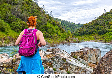 Girl Standing on Rocks Near Fast River