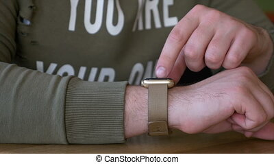 Closeup of man interacting with smartwatch in a restaurant