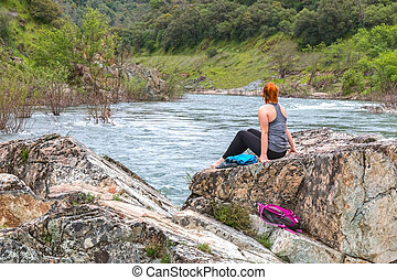 Girl Sitting on Rocks Near Fast River