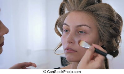 Makeup artist applying liquid tonal foundation on woman's...