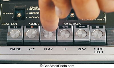 Finger Presses Play, Stop and Record Control Buttons on...