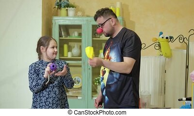 The clown shows the girl a trick with magic bottles and a...