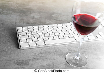 Red wine and computer keyboard on concrete table with focus...