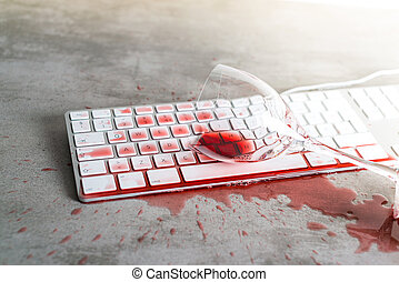 Red wine spilled over computer keyboard on concrete table -...