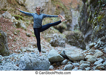 Young woman doing yoga in a canyon