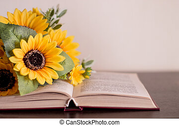 Opened book with flowers on a wood table.