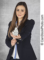 Smiling business woman gives a small house