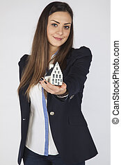 Smiling business woman showing house