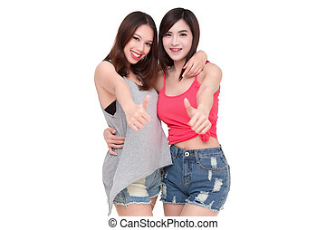 Two smiling asian women giving thumbs up