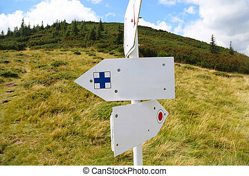 Mountain trail markings, empty sign-boards with mountain vegetation background