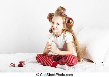 Portrait of a lovely little girl with big curlers on her...