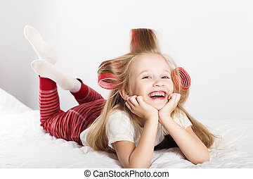 Beautiful little girl with curlers on her head looking at...