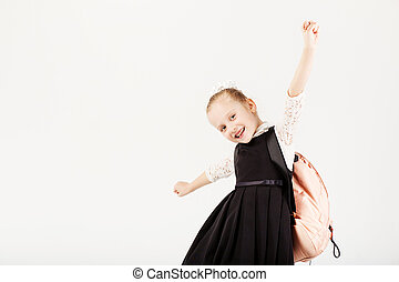 Funny smiling little girl with big backpack jumping and having fun against white background
