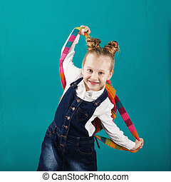 Funny smiling little girl with big backpack jumping and having fun against blue wall