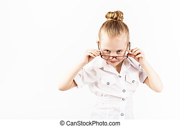 Funny little girl wearing eyeglasses imitates a strict teacher against white background