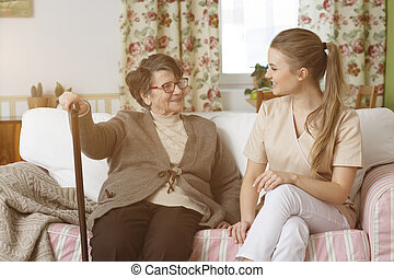 Caregiver and woman sitting on a sofa - Young caregiver and...