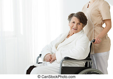 Elderly woman on wheelchair - Smiling elderly woman sitting...