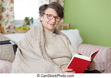 Senior woman reading a book - Smiling senior woman sitting...