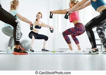 Exercising with kettlebells - Young fit women on fitness...