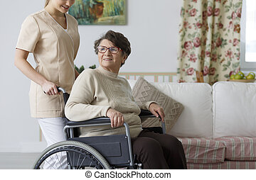Woman on wheelchair and her nurse - Smiling elderly woman on...