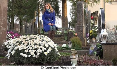 sad woman wife sit on bench in city cemetery in autumn time....