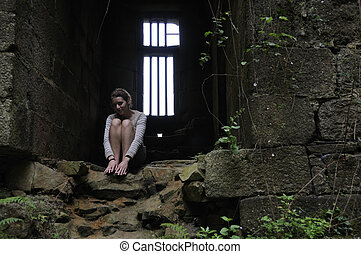 Dungeon - Young woman sitting in dungeon of old castle in...