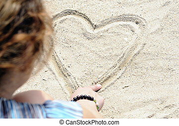Holiday flirt - Young woman drawing heart in sand at the...