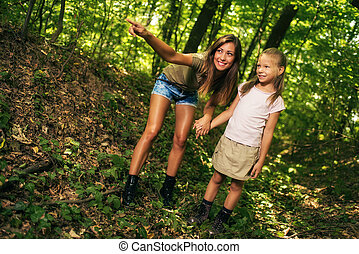 Young Woman And Girl In The Forest - Beautiful young mother...