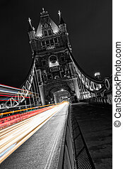 Tower Bridge in London in black and white, UK at night with blur colored car lights.