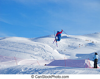 young skier in blue performing a tele-heli jump