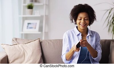 woman with smartphone and headphones at home - leisure,...