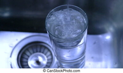 Pure water is poured into a glass, in the kitchen, in the sink.