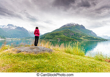 Woman tourist relaxing on fjord sea shore, Norway - Travel...