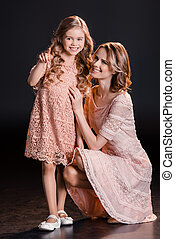 Beautiful happy mother and daughter in pink dresses pointing...