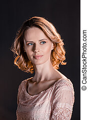 Portrait of beautiful young woman in pink dress looking away...